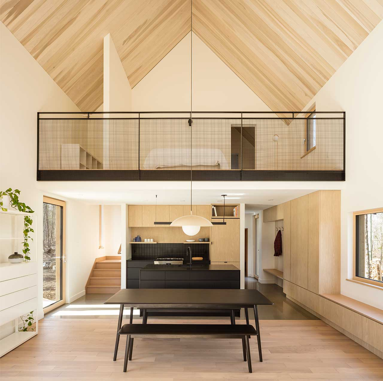 double-height modern living space of cabin with loft bedroom
