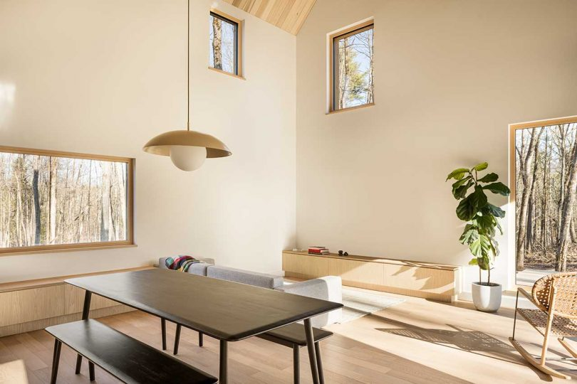 double-height living room in cabin with light woods and sparse furnishings