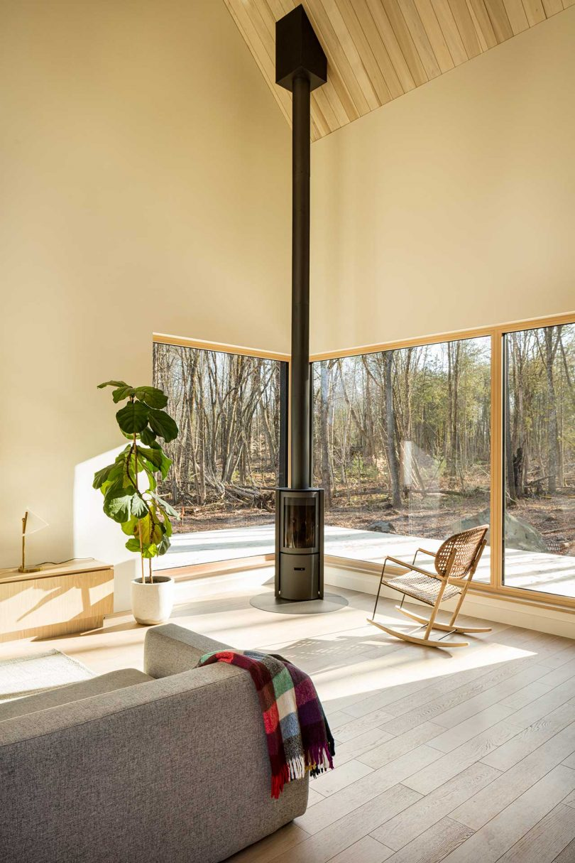 corner of modern living room in cabin with windows looking out to forest