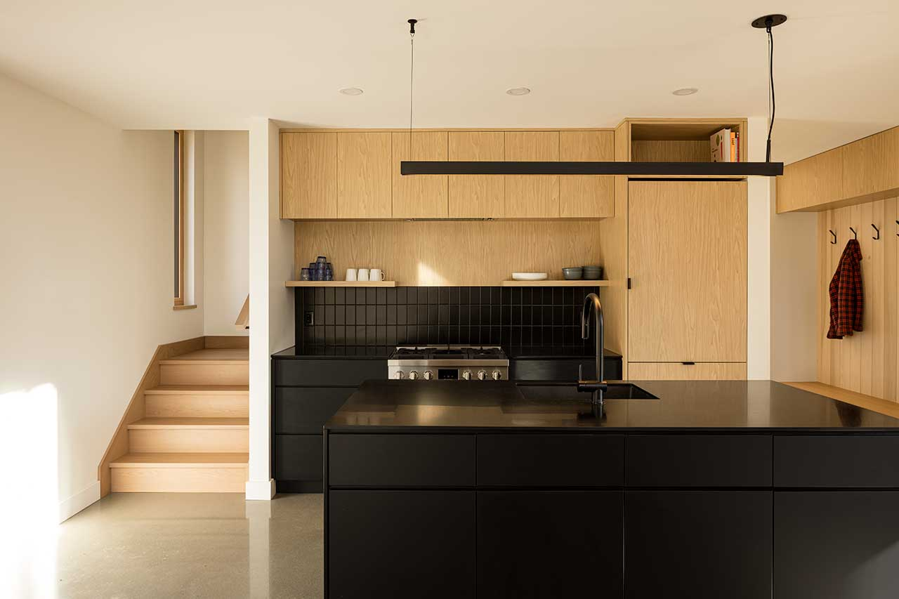 compact modern kitchen in black and wood tones