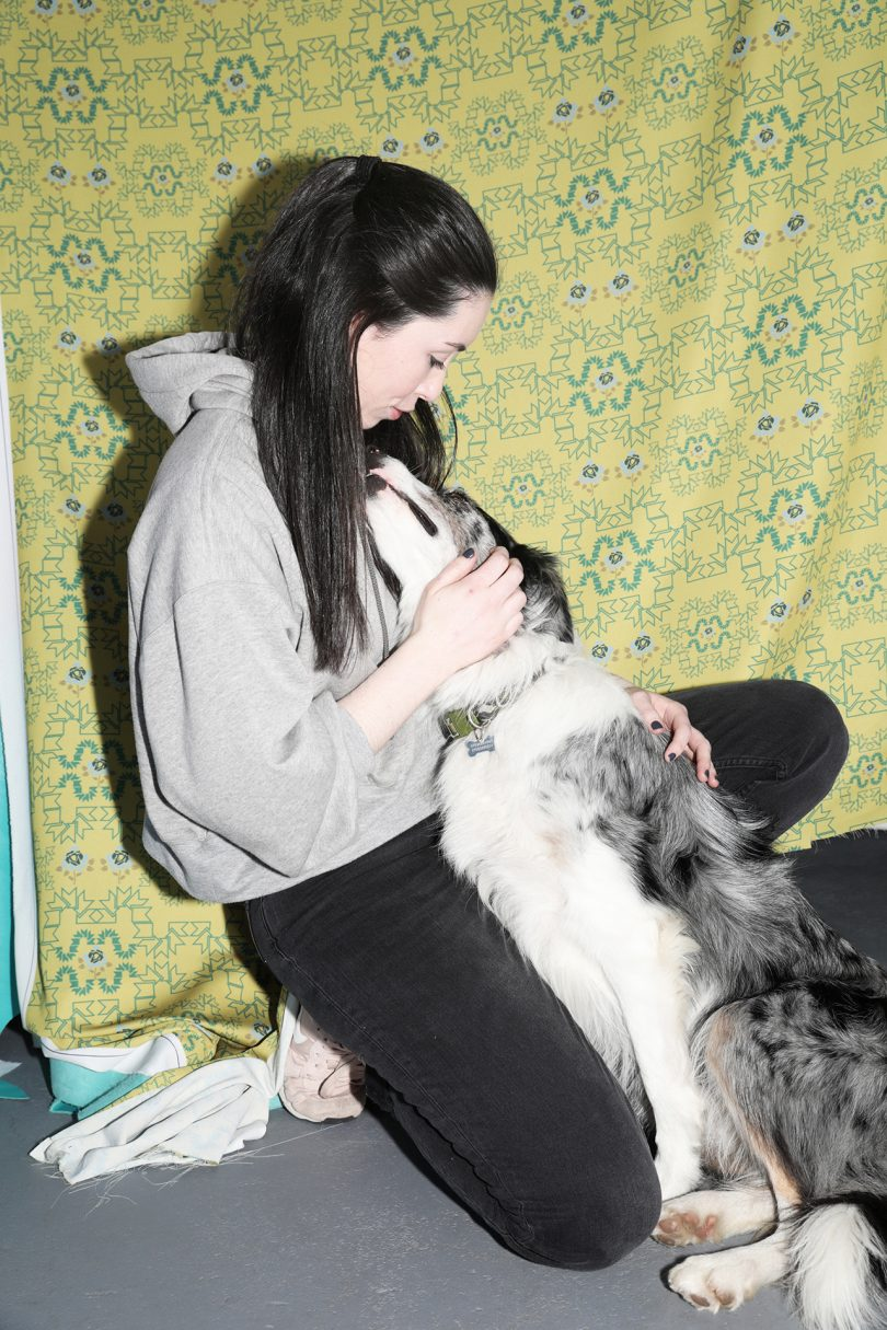 light skinned woman with long dark hair wearing sweats and cuddling with a dog