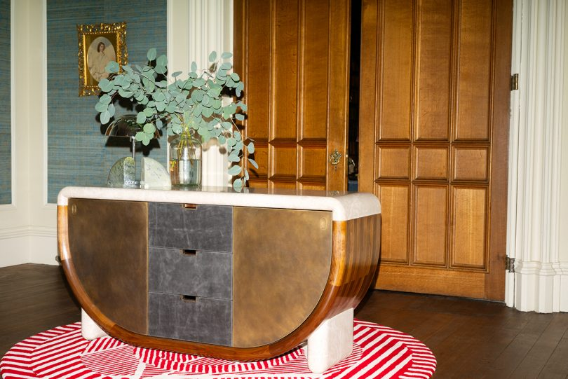 wood and marble credenza with vase of greenery in front of large wood doors