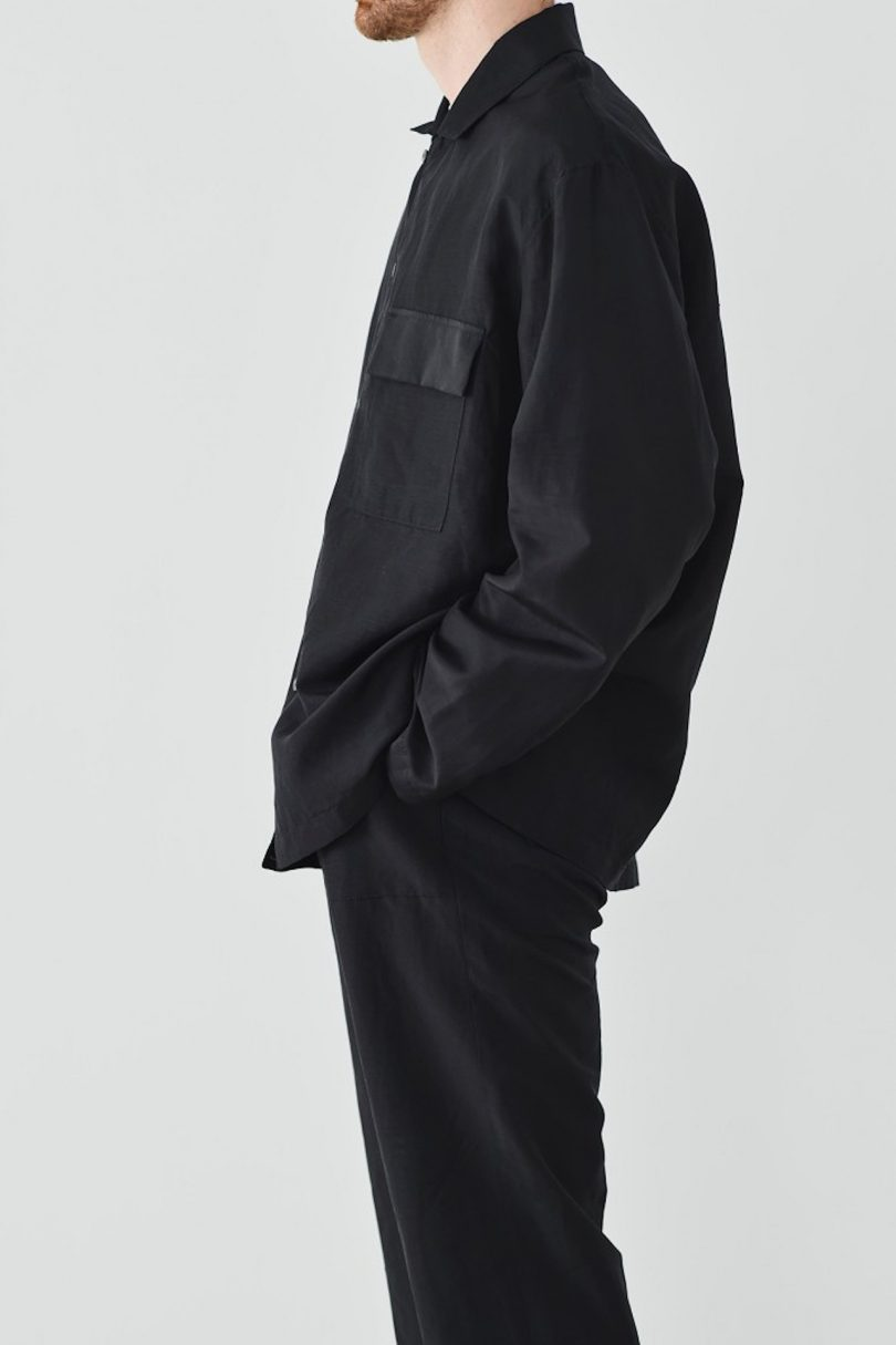 male model standing to the side wearing all black clothing