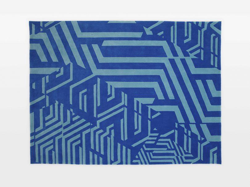 rectangular blue floor rug with geometric pattern on white background