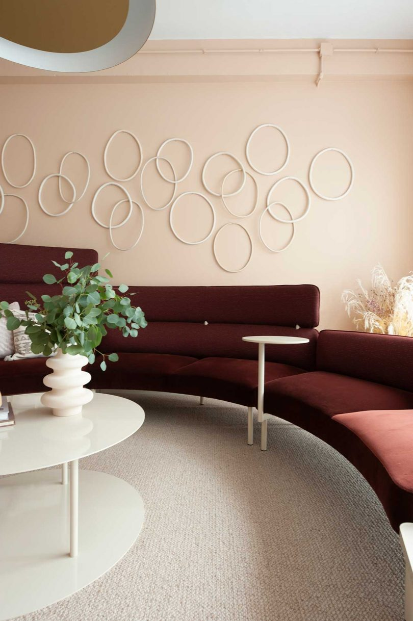 modern seating area with burgundy curved sofa