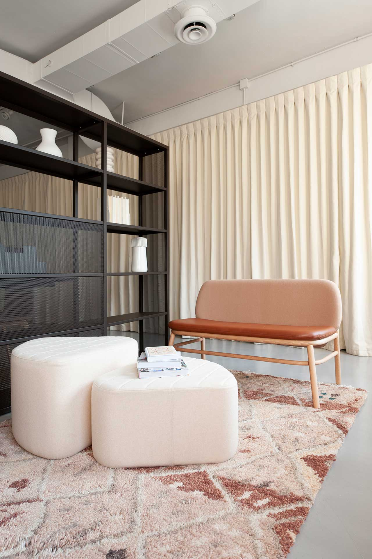 sitting area with modern settee and footstools by large black shelf