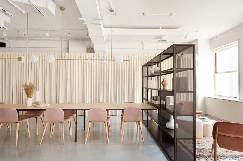 modern conference space with long table, pink chairs and black bookcase