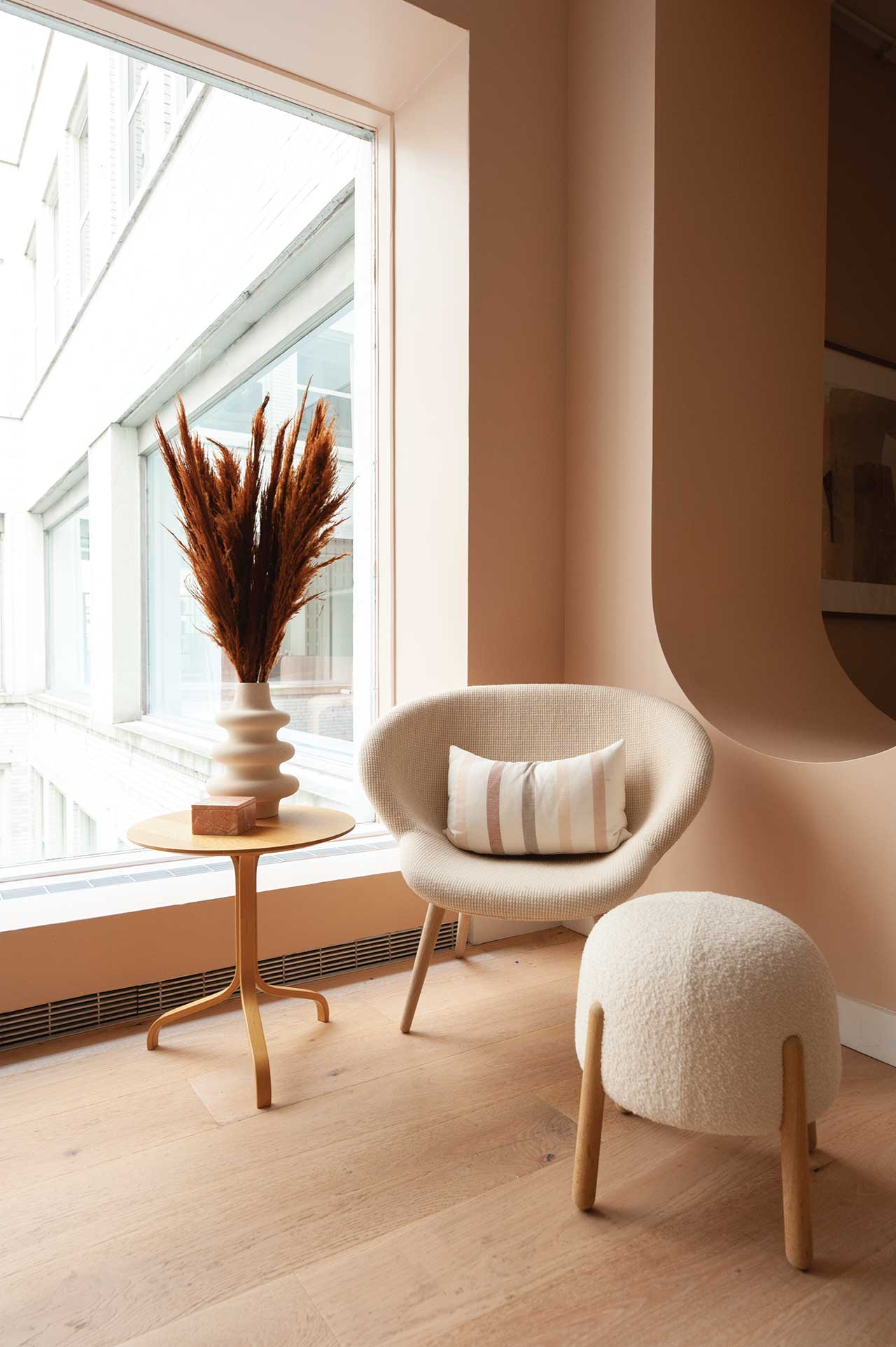 seating nook with cream colored chair and footstool