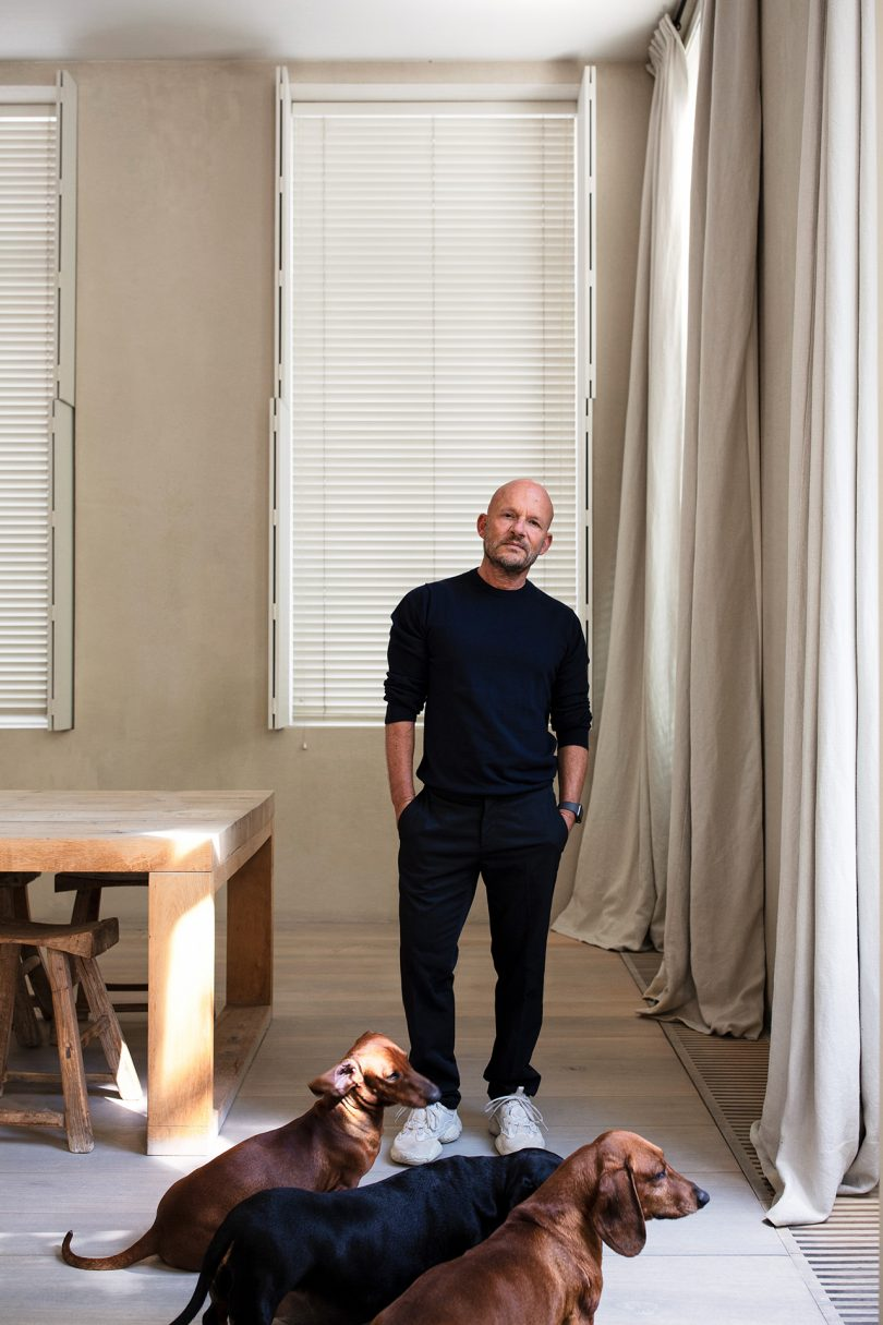 light-skinned bald man with facial hair wearing all black with three dogs by his feet