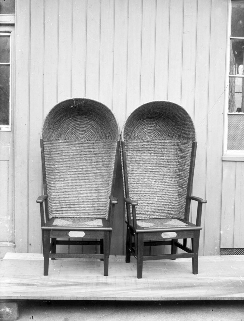 black and white image of two side by side hooded armchairs outside