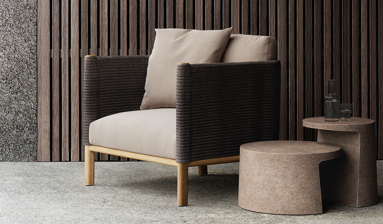 boxy outdoor armchair with pillows and two side tables