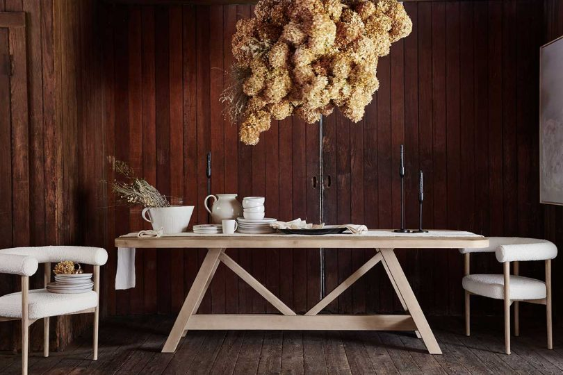 light wood dining table in front of dark wood paneled wall