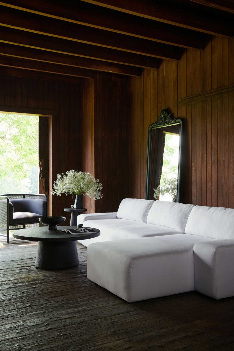 dark wood paneled living space with white sofa