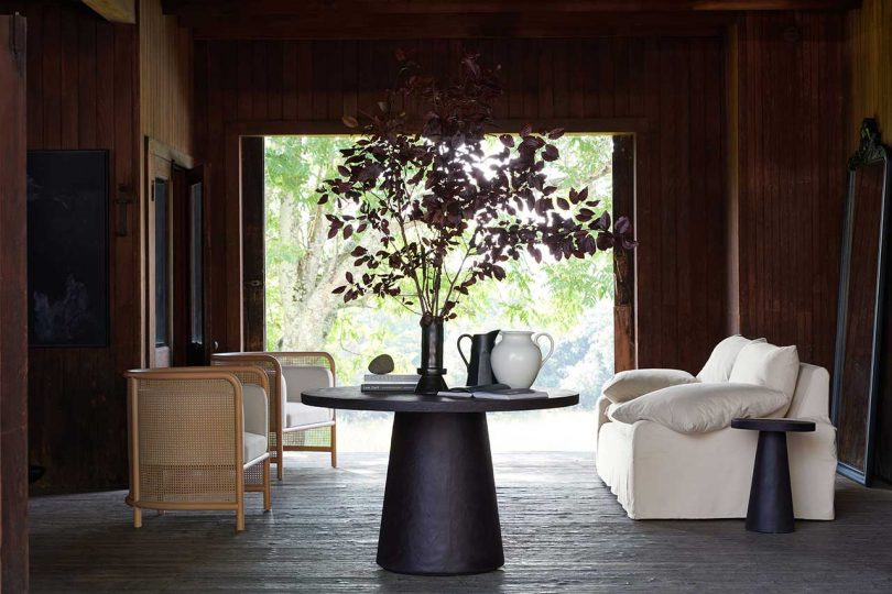dark wood paneled living space with white sofa and rattan settee