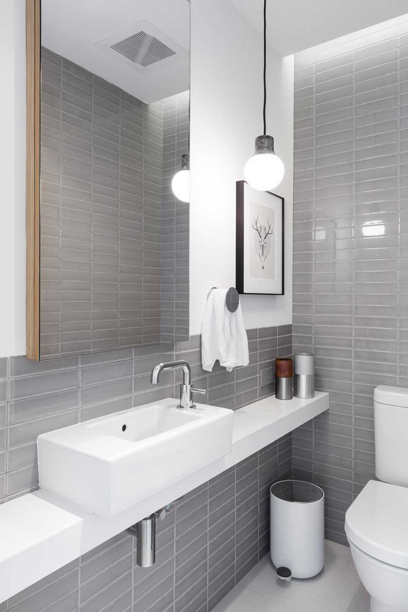 simple bathroom with gray tile and white fixtures