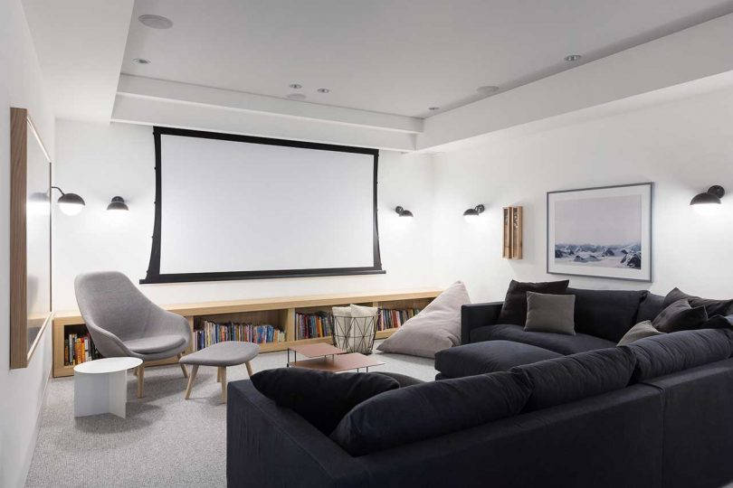 modern screening room with black sofa and white walls