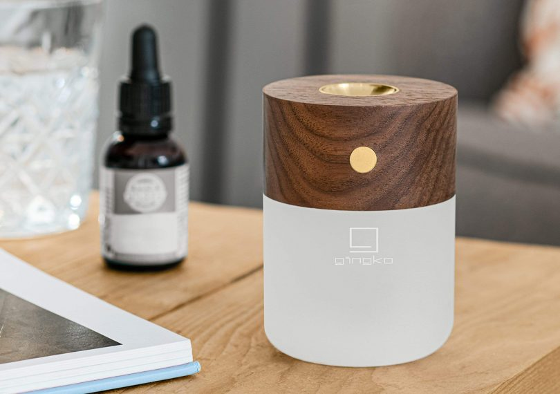 Gingko smart diffuser lamp on a side table with essential oils in the background