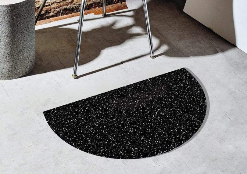 Speckled black half circle mat by slash objects on the ground next to a chair
