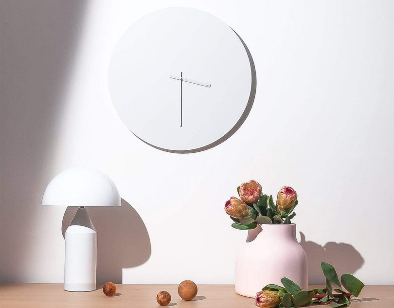 TOO designs minimal wall clock in white hanging over a table with a white lamp and vase full of flowers
