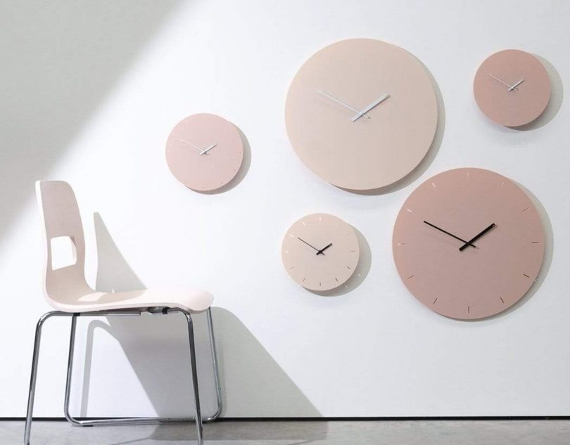 TOO Designs minimal wall clocks in almond cream with a chair in front of the wall